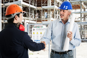 Two workers shaking hands in a construction site
